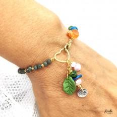 Pulsera en mano de cristales verdes, corazon en acero, y colgantes de piedras de rio y una hoja en arcilla