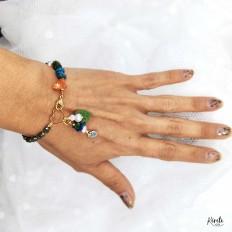 Imagen de mano de mujer luciendo una pulsera de critales y hojitas con perlas de rio, fondo blanco mano estirada