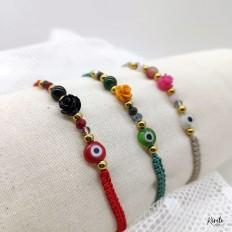 Pulseras en exhibición de colores, rosas y ojo protector en tres colores diferentes