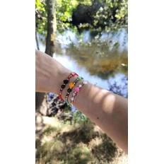 Imagen con fondo del rio tambre en santiago de composstela, mano luciendo 3 pulseras kerete de colores diferentes
