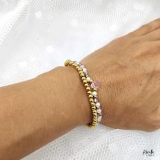 Imagen de mano con la pulsera elasticada de cristales y otra de bolitas en acero con baño en oro