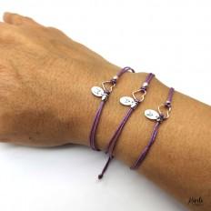 Imagen de tres pulseras mila, las tres en una mano con corazones y diferentes iniciales en plata