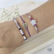 Muñeca de mujer luciendo 3 pulseras en color malva con cristales, estrella y una inicial personalizada