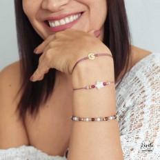 Mano de joven sonriendo con sus tres pulseras color lila de cristales