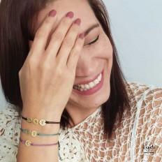 Chica feliz con sus pulseras en la muñeca, pulseras verde, negro y lila