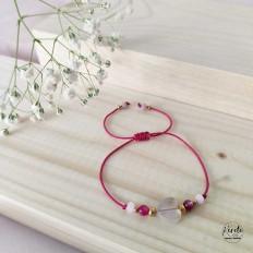 Pulsera de hilo rosa con un corazon en cuarzo rosa, la pulsera es regulable y esta sobre una tabla de madera