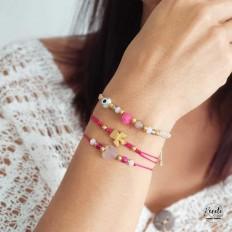 Mano de señorita con tres pulseras de color fuxia, con un ángel y cristales