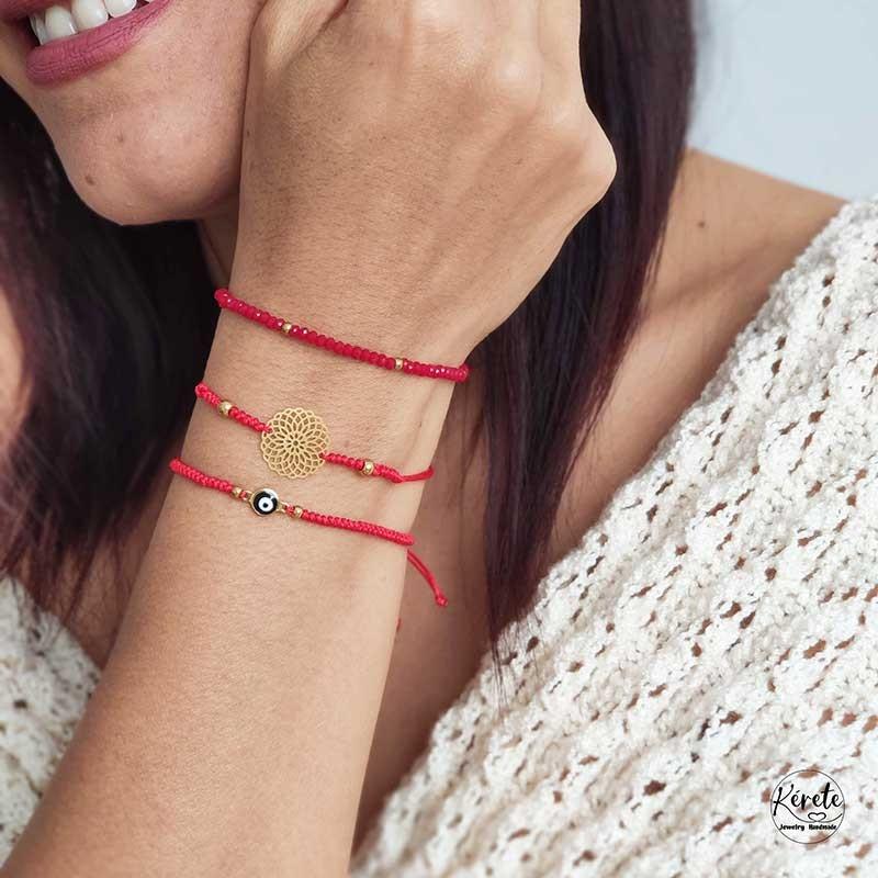 Chica sonriendo con tres pulseras rojas en s u muñeca