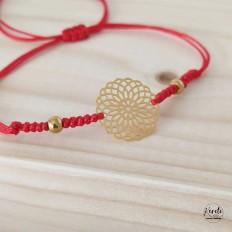 Pulsera tejida con nudos roja y un centro de mandala y bolitas de acero doradas