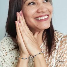 Chica feliz con las manos juntas mostrando en cada una una pulsera de colores e inicales