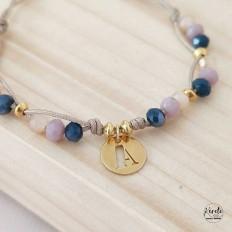 Foto de pulsera con cristales entrelazados lila y azul con un dije central colgante de inicial, con un fondo de madera natural