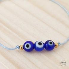 Imagen de producto de pulsera regulable con 3 ojitos turcos azules y cordon celeste