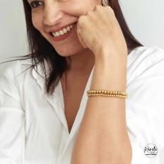 Mujer luciendo 2 pulseras doradas en brazo