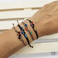 Mano de mujer con cuatro pulseras de hilos con  piedras de colores